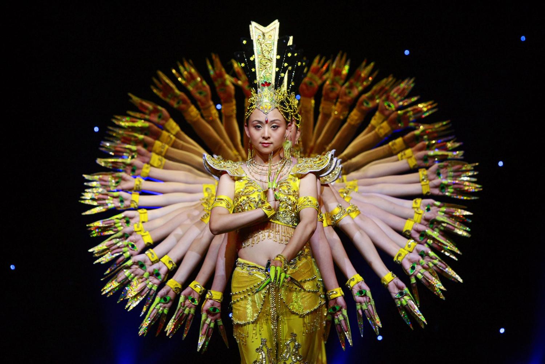 Таи Лихуа /в средата/, арт директор на Китайската асоциация на инвалидите води трупа от танцьорки с увреден слух изпълняващи танц направлявани от жестовете на ръцете. Изпълнението е в подрепа на правата на хората с увреждания по света.