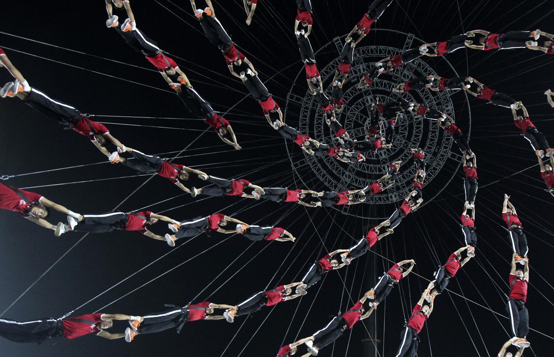 Студенти от Шаолин Тагу - училището по бойни изкуства във въздуха на генерална репетиция за спектакъл на каскадьори. 2014 Nanjing младежки олимпийски игри, на стадиона в Nanjing на 14 авг 2014