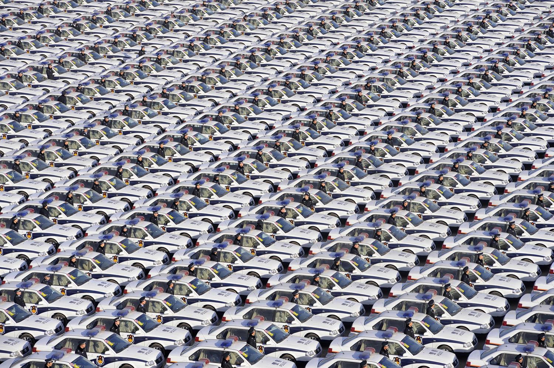 стотици полицаи стоят редом до чисто нови полицейски автомобили, предоставяни от местната власт, за да се гарантира обществената сигурност през новогодишните празници по време на церемония по предаването им в Тайюан, провинция Шанси, на 30 декември, 2009