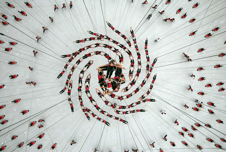 Студентите от Шаолин Tagou Карате клуб са хванати във въздуха, на репетиция за спектакъл на каскадьори на церемонията по откриването на 2014 Nanjing младежки олимпийски игри, на стадиона в Nanjing на 09 август 2014