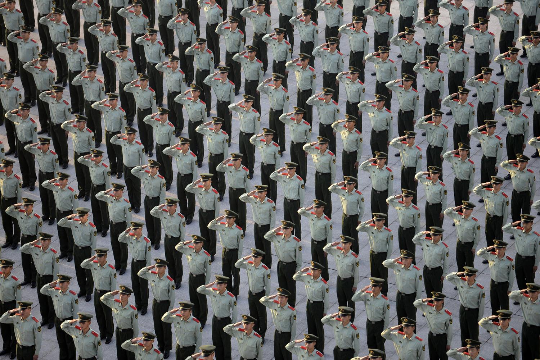 Паравоенни полицаи отдават чест на церемонията по вдигане на знамето, по случай 65-ата годишнина от основаването на Китайската народна република, в Нанкин, провинция Дзянсу, на 1 октомври 2014 година.