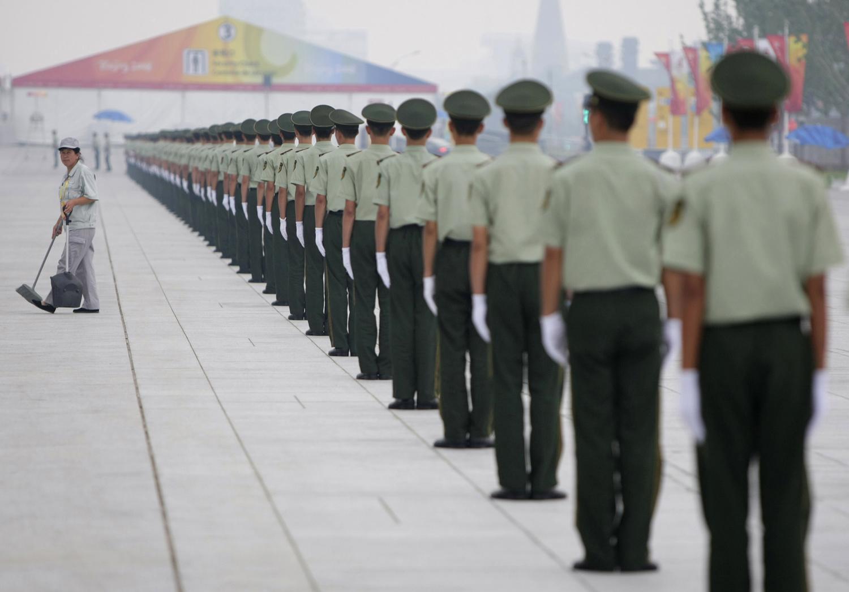 Китайски параваоенни служители в  редица до честачка. Олимипийски игри в Пекин  2008