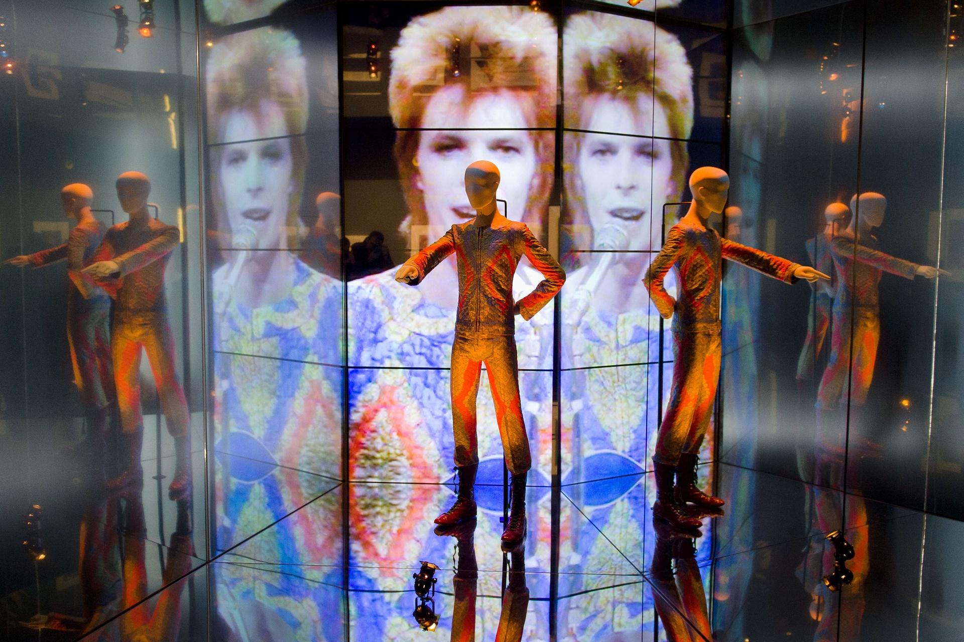 """През 2013 г. музеят Виктория и Албърт провежда изложба с над 300 предмети на Дейвид Бауи, включително ръкописни текстове, оригинални костюми, мода, фотография, кино, музикални клипове, определени проекти и собствени инструменти на Бауи. Тук е костюма """"Starman"""". Снимка: Leon Neal / AFP / Getty Images"""