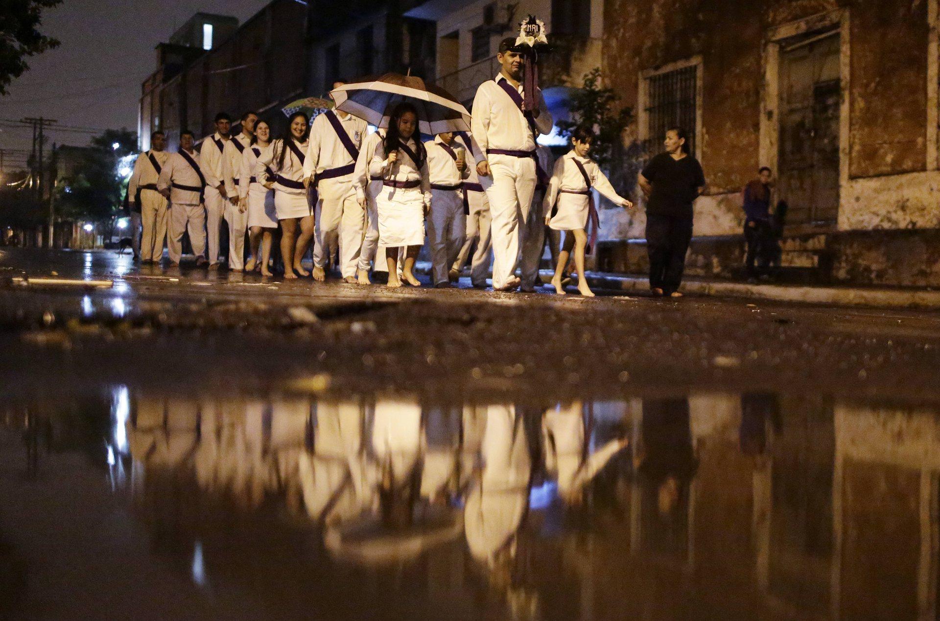 Асунсион, Парагвай Католици ходят боси в дъжда, пеещи религиозни песни по време на шествие из града Фото: Хорхе Саенц / AP