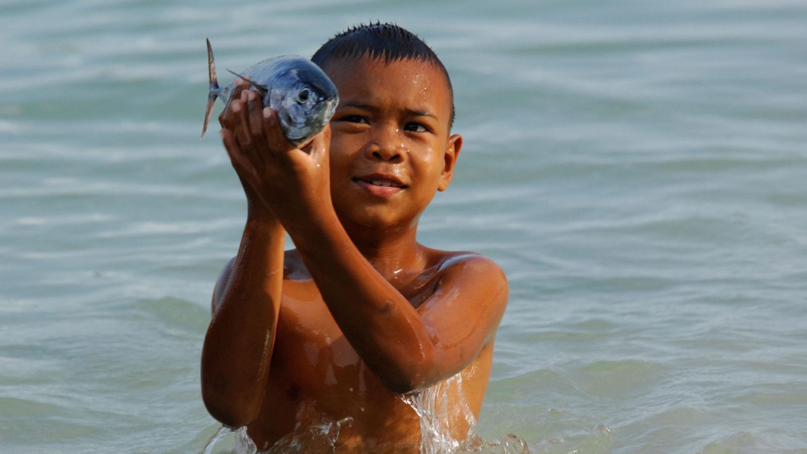 BKT7JB young sea gypsy boy holding fish, chao leh, sea gypsy village , rawai beach , phuket island ,thailand