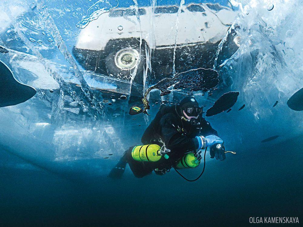 Водолаз плува под прозрачен лед (1 метър дебелина) с превозно средство над него. Езерото Байкал.